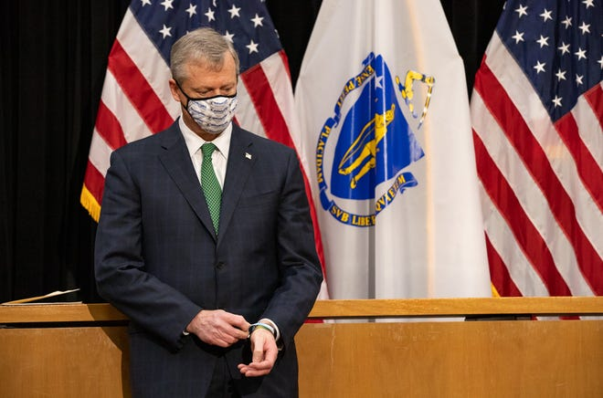 Gov. Charlie Baker looks down and fiddles with his rubber bracelets Tuesday after announcing additional restrictions and economic reopening rollbacks in the midst of a troubling COVID-19 surge.