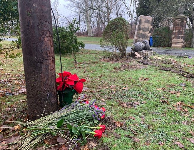 Flowers are placed at the base of a utility pole near Brenton Road in Newport, the scene of a fatal accident early Saturday morning.