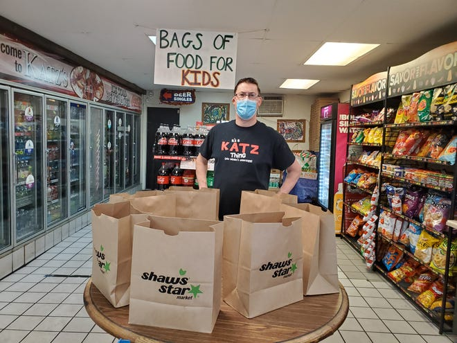 Michael Katz, owner of Katz's Deli and Market in Dover, stands by bags containing lunch foods. Kids can come in and take a bag at no charge.