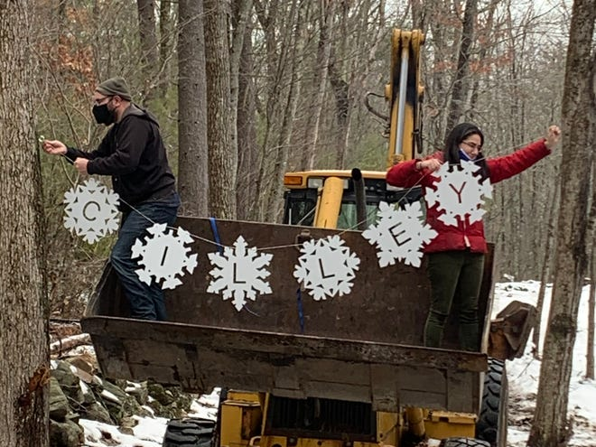 Josh and Emilie Cilley decorate a newly created Christmas trail at Bruce and Jackie Cilley's home in Barrington, a new holiday tradition born in response to the coronavirus pandemic.