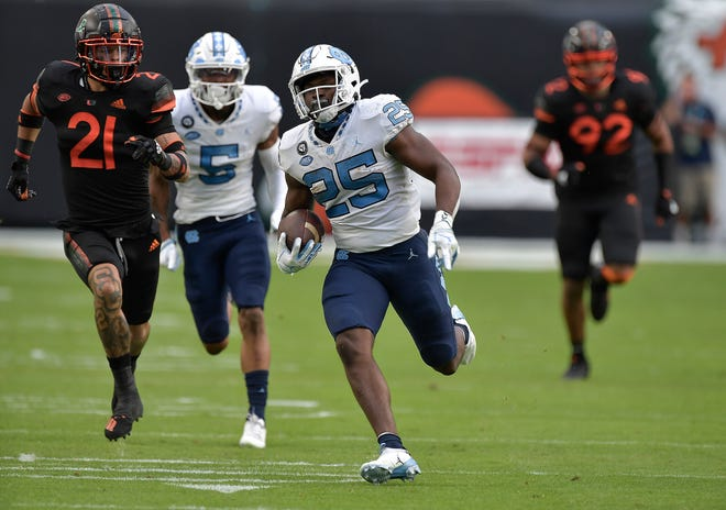 North Carolina running back Javonte Williams sprints away from the Miami defense during the Tar Heels' 62-26 rout of the No. 9 Hurricanes on Saturday