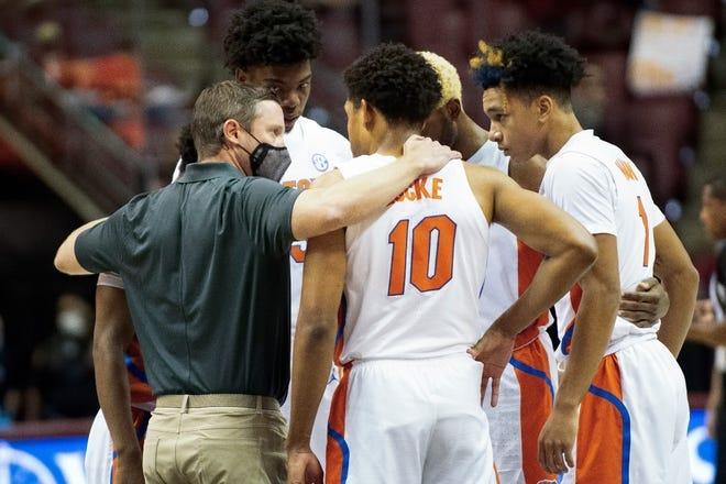 The Florida Gators huddle with coach Mike White after Keyontae Johnson collapsed during Saturday's game against Florida State in Tallahassee.
