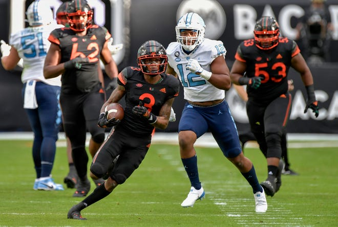 Miami receiver Mike Harley runs ahead of North Carolina linebacker Tomon Fox during the first half of their game, Saturday, December 12, 2020, at Hard Rock Stadium.