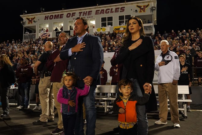 Florida Gov. Ron DeSantis attends the Niceville-Edgewater high school football playoff game in Niceville on Friday. Like others in the crowd at the outdoor game, the governor declined to wear a face mask during the pregame ceremonies, even as coronavirus infection numbers rose by more than 11,600 that day.