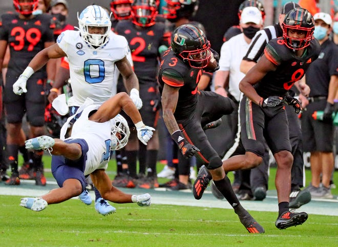 Miami Hurricanes wide receiver Mike Harley (3) catches the ball as North Carolina Tar Heels defensive back Trey Morrison (4) gets horizontal in the first quarter at Hard Rock Stadium In Miami Gardens, Florida, Saturday, December 12, 2020.