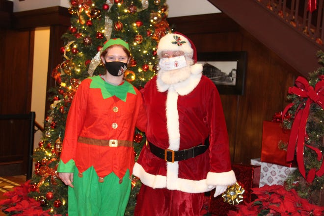Taylor Devilbiss poses for a photo with Santa Claus on Friday, Dec. 11 at the Hotel Pattee.