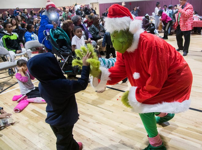 The Grinch makes an appearance at the annual Christmas Party at Sierra Vista Community Center in south Stockton on Dec. 20, 2018.