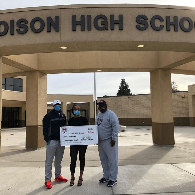 Edison football coach Booker Guyton, right, and interim principal Monica Gayle, center, pose with a $6,000 grant check from the NFL Alumni.