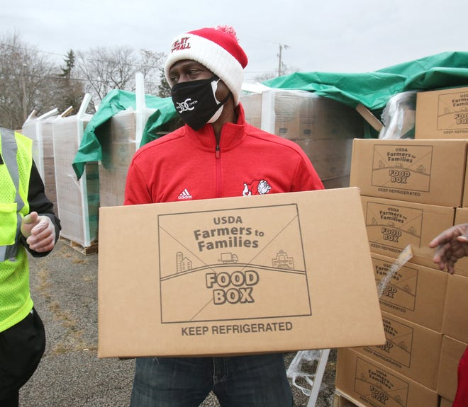 Ronnie Stokes unloads a box as Canton Outside of Canton provided food at St. Paul AME Church in Canton on Saturday. A group of former professional athletes and business people who grew up here and moved away provided food for needy families.