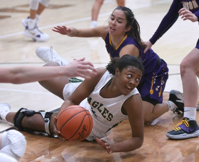 GlenOak's Aniyah Hall (center) looks to pass the ball while being guarded by Jackson's Halle Ignacio (rear) during Friday's game.