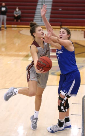 Walsh's Mayci Sales (22) puts up an underhand shot while being guarded by Hillsdale's Sydney Mills (5) during Saturday's game.