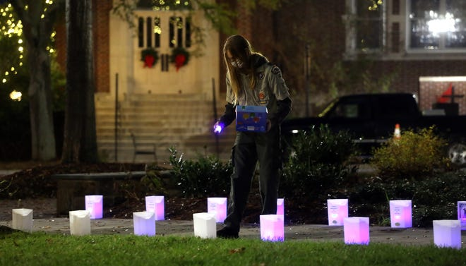 Will Greene of Bot Scout Troop 402 volunteers his time to place candles in luminaries for Hospice's annual Lighting the Way event in uptown Shelby.