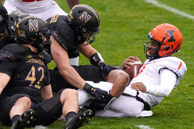 Illinois quarterback Isaiah Williams, right, is tackled by Northwestern defenders during the first half in Evanston, Saturday. [NAM Y. HUH/THE ASSOCIATED PRESS (AP Photo/Nam Y. Huh)