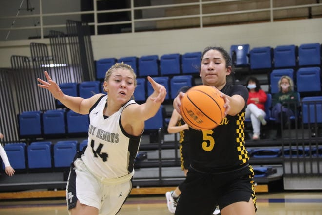 Tecumseh's Tawny Billy (right) and Perkins-Tryon's Karmen Jones lunge for the basketball Friday in the semifinals of Bethel High School's First United Bank Classic at the B.E. Cantrell Fieldhouse.