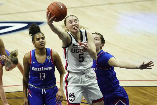 UConn's Paige Bueckers (5) drives to the basket past UMass Lowell's Sydney Coombs, right, and Kaylen Banwareesingh during the first half on Saturday in Storrs.