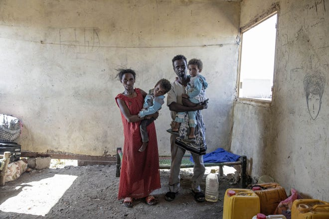 Tesfaalem Germay, 34, an ethnic Tigrayan survivor from Mai-Kadra, Ethiopia, poses for a photograph with his wife Bethlehem, 21, and their twin daughters inside a temporary shelter Nov. 22 at Village 8, the transit center near the Lugdi border crossing, eastern Sudan.