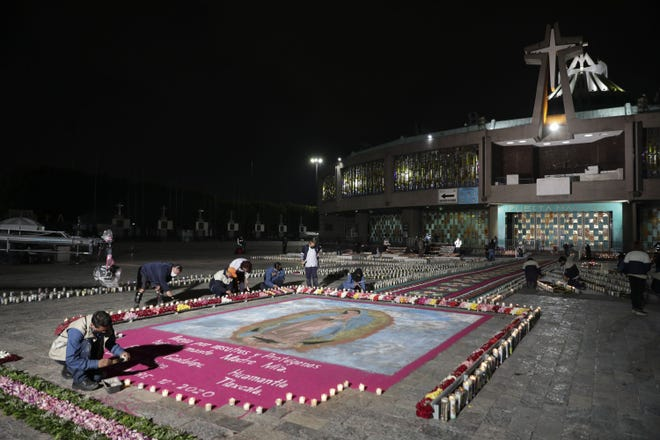 A man lights a candle next to an image the Virgin of Guadalupe Friday outside the Basilica of Guadalupe in Mexico City.