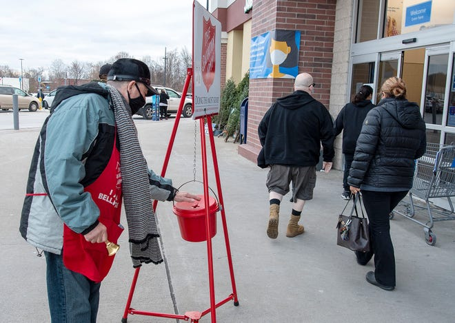 Walter Tubens tucks a donated bill into the bucket while ringing a bell for the Salvation Army Tuesday outside Walmart in Worcester.
