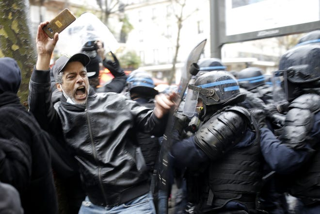 Riot police officers charge a man holding his phone during a protest Saturday in Paris.