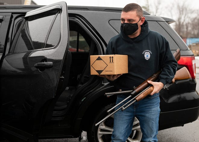 Southbridge Police Det. Evan Genkos delivers the guns they gathered from the Goods for Guns Buyback on Saturday to City Welding and Sheet Metal Fabrication in Worcester, where owner Paul Curci crushed the unwanted weapons with heavy machinery.