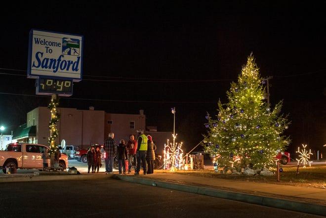 Orang-orang berkumpul di sekitar pohon yang dinyalakan selama Sanford Shines, upacara penerangan pohon untuk merayakan banyak keberhasilan yang terkait dengan pembangunan kembali komunitas di Sanford pada 11 Desember 2020.