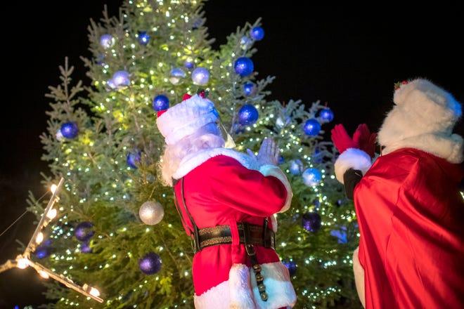 Santa dan Nyonya Klaus bereaksi setelah menyalakan pohon.