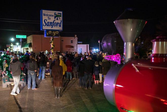 Orang-orang berkumpul di sekitar pusat kota Sanford selama Sanford Shines, upacara penerangan pohon untuk merayakan banyak keberhasilan yang terkait dengan pembangunan kembali komunitas di Sanford pada 11 Desember 2020.