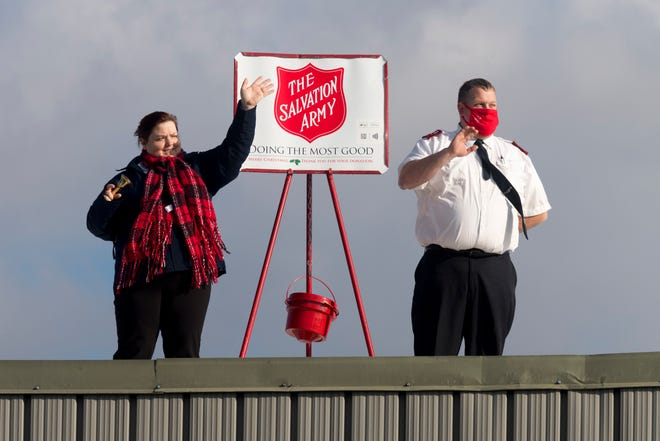 Salvation Army Captains Crystal and Benny Carringer wave to cars from the roof of the Salvation Army Center of Hope on Washington Street in Henderson as they ring the bell for donations with a goal of raising $12,000 in 12 hours Saturday morning, Dec. 12, 2020.