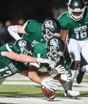 Trinity's Jack Dingle helps recover a blocked punt for an early touchdown in the 6A semifinal game Friday night. The Rocks rolled past the Tigers 31-0. Trinity is now 9-0 and faces Male (8-1) in state final at the University of Kentucky's Kroger Field.