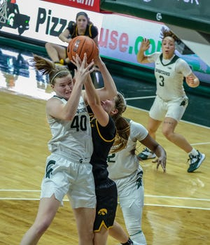 MSU's Julia Ayrault (40) battles Iowa's Kate Martin in a Big Ten matchup at Breslin Center Saturday, Dec. 12, 2020. The Spartans held on to win 86-82.
