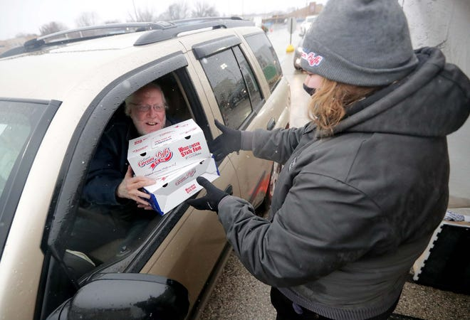 Christie Bailey, of The Original Cream Puffs, hands out a box of Cocoa Cream Puffs during a curbside pickup event on Saturday, Dec. 12, 2020.