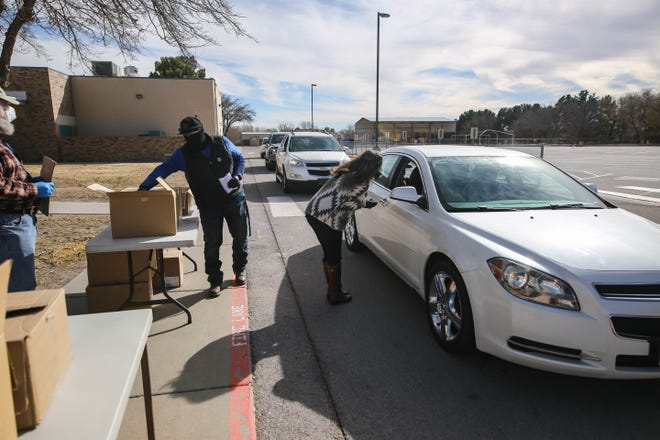 Tessa Abeyta Stuve, a member of the Las Cruces City Council, hands out food vouchers and masks at a Mask Up Las Cruces free drive-thru mask giveaway for adults and kids at Mesilla Park Elementary in Las Cruces on Saturday, Dec. 12, 2020.