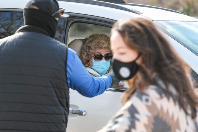 Tessa Abeyta Stuve, a member of the Las Cruces City Council, hands out food vouchers and masks at a Mask Up Las Cruces free drive thru mask giveaway for adults and kids at Mesilla Park Elementary in Las Cruces on Saturday, Dec. 12, 2020.