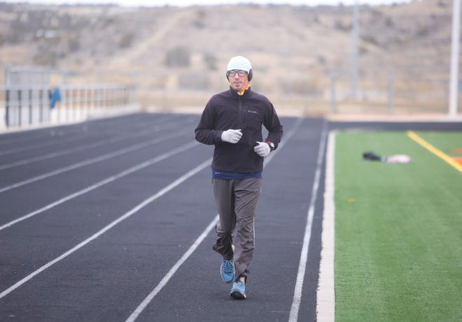 Attorney Ryan Lane completes lap No. 125 of 400 on Saturday, Dec. 12, 2020, at Fred Cook Memorial Stadium in Aztec. Lane embarked on the challenge as a way to show local youth that they can overcome trying times like the COVID-19 pandemic, both physically and mentally.