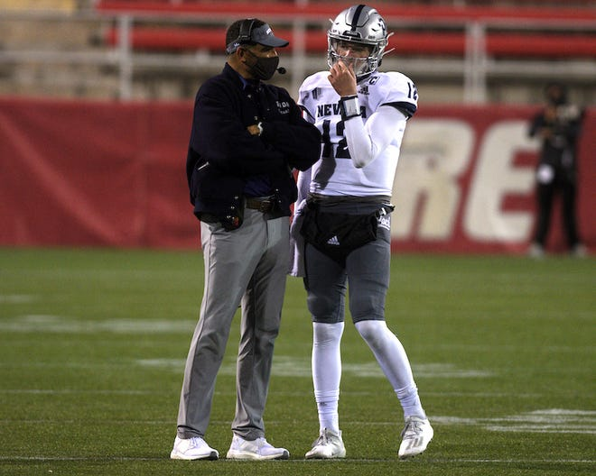 Nevada head coach Jay Norvell confers with quarterback Carson Strong during Friday night's game in Las Vegas.