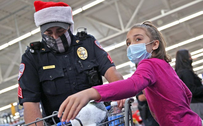 Eliana Jackson, right, and SAPD Sergeant Michael Gaeta, left, shop at the Walmart on N. Bryant St. during the annual Blue Santa event Saturday, Dec. 12, 2020.