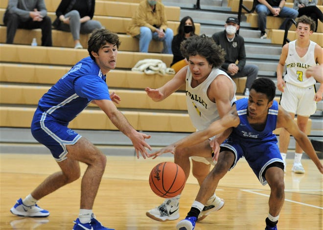 Tri-Valley's Ty Smith battles with two Olentangy Berlin defenders for possession in Saturday's game. The Scotties lost 53-50.