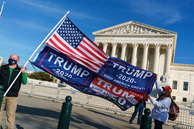 Kathy Kratt of Orlando, Fla., right, displays her Trump flags as she and other activists demonstrate their support for President Donald Trump at the Supreme Court in Washington, Friday, Dec. 11, 2020. (AP Photo/J. Scott Applewhite) ORG XMIT: DCSA116