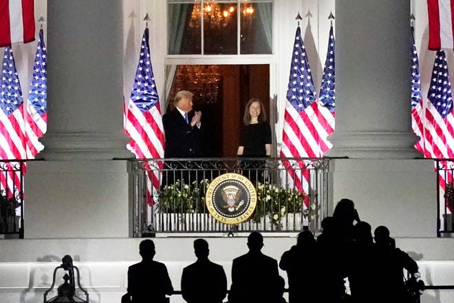 President Donald Trump applauds Amy Coney Barrett as they stand on the Blue Room Balcony after Supreme Court Justice Clarence Thomas administered her the Constitutional Oath on the South Lawn of the White House in Washington, Monday, Oct. 26, 2020.