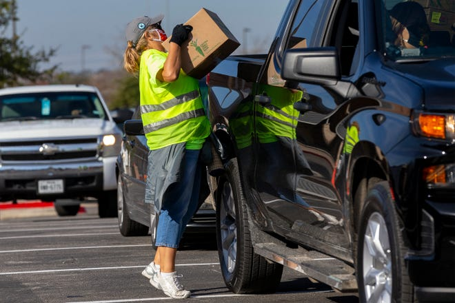 Volunteer Brenda Kolas loads food into a vehicle at Lehman High School in Kyle on Dec. 12.