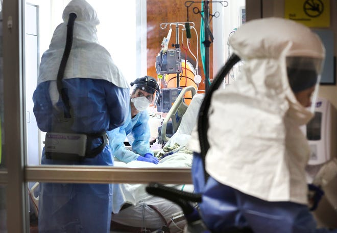 Nurse Lauren Walters, center, talks with Dr. Charles Burch, left, before performing intubation on a patient in the Methodist Hospital COVID Unit, on April 23.