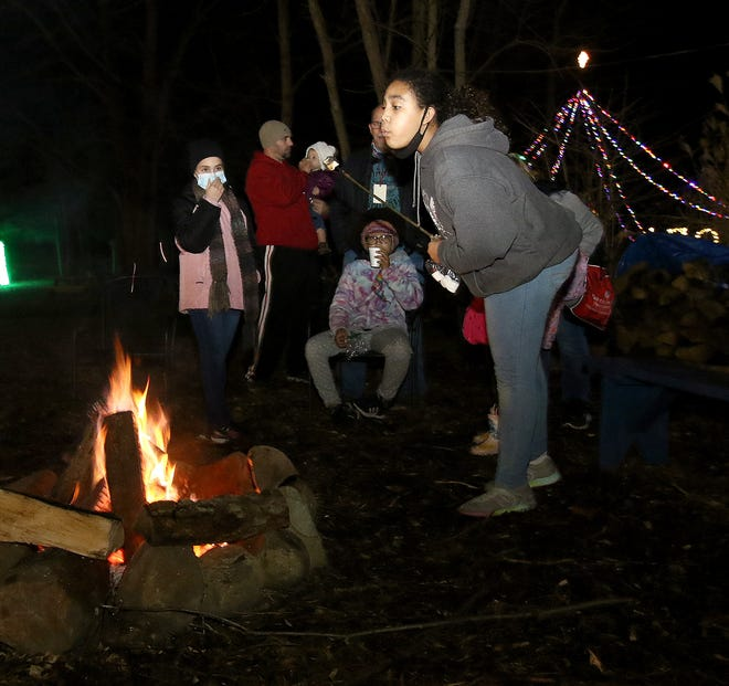 Zari Itangata, 11, from Perry Township, blows out the flame on a roasted marshmallow Friday night at a campfire stop during Holiday Nights at Beech Creek Botanical Garden & Nature Preserve.