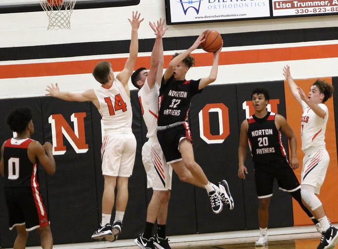 Marlington's Tommy Hippely, center, and Casey Miller (14) defend against a shot attempt by Norton's Eli Hirst during action at Marlington High School Saturday, December 12, 2020.