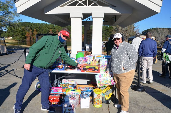 Director of golf Charlie Kent collects a new, unwrapped toy from a resident for donation to Bluffton Self Help.