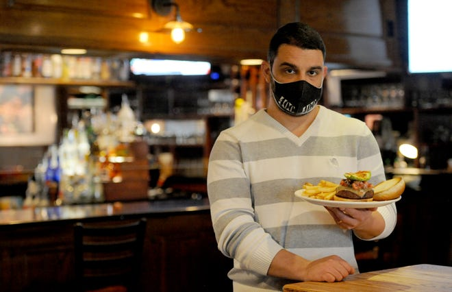 Rich Hristov, general manager at the 400 East Restaurant & Bar, holds a California burger plate, one of the popular items on the fall menu at the East Harwich restaurant.