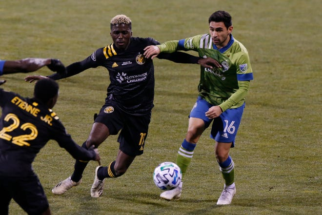 Columbus Crew's Gyasi Zardes, left, and Seattle Sounders' Alex Roldan chase a loose ball during the first half of the MLS Cup championship match Saturday night in Columbus, Ohio.