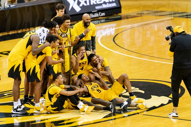 Missouri players and coach Cuonzo Martin pose with the Braggin' Rights trophy after they defeated Illinois on Saturday night at Mizzou Arena.