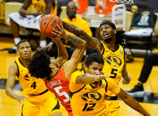 Missouri forward Mitchell Smith (5) reaches to defend a shot by Illinois guard Andre Curbelo (5) behind Missouri guard Dru Smith (12) during a game Saturday night at Mizzou Arena.