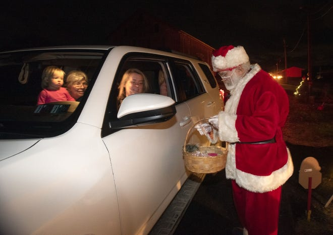 A mask-wearing Santa hands out treats Saturday night at the Hookstown Christmas Drive-Thru, sponsored by South Side Historic Village Association, Hookstown Grange and local churches. [Sally Maxson/For BCT]