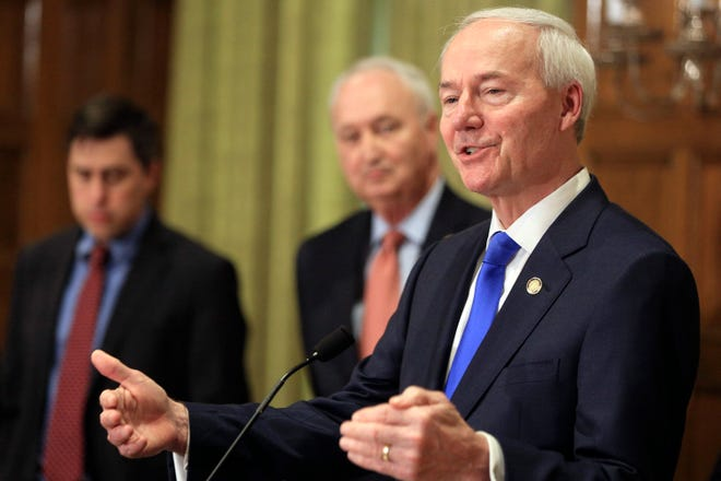 """In this March 23, 2020 file photo, Gov. Asa Hutchinson, right, speaks along with Larry Walther, middle, Secretary of the Department of Finance and Administration and Jake Bleed, state budget director in Little Rock, Ark.  Congressional Republicans say they are against providing additional coronavirus aid to state and local governments because they claim it would """"bail out"""" states run by Democrats. But the pandemic-induced tax drop-off is hitting Democratic and Republican states alike. Among states hit hard are those led by Republicans, including energy-dependent Alaska, North Dakota and Wyoming, and tourism-heavy Florida. (Staton Breidenthal/The Arkansas Democrat-Gazette via AP)"""